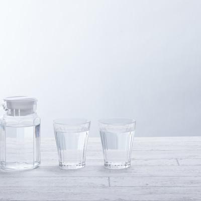 「テーブルに置かれたグラスとミネラルウォーター」の写真素材
