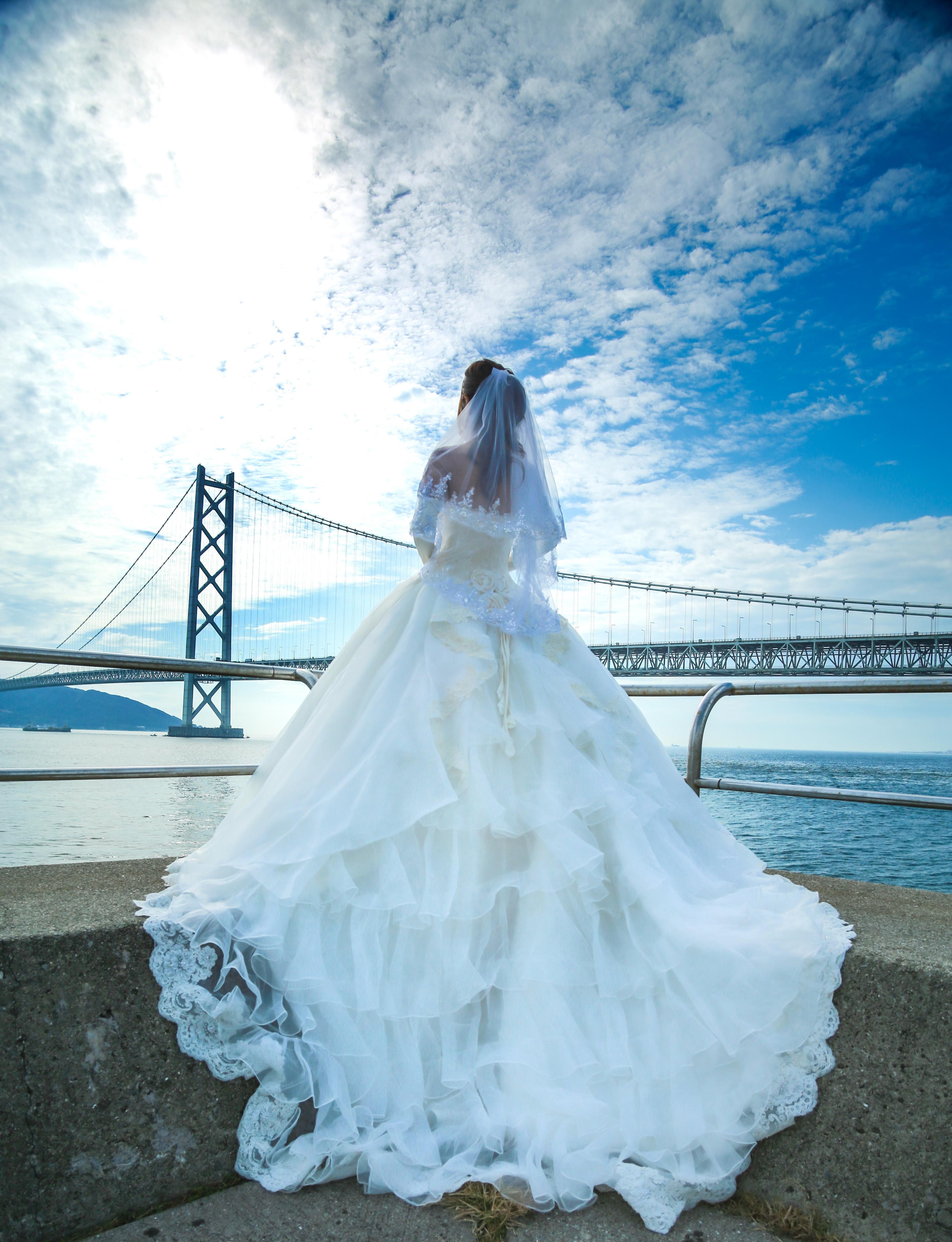 「明石海峡大橋とウェディングドレス姿の女性」の写真