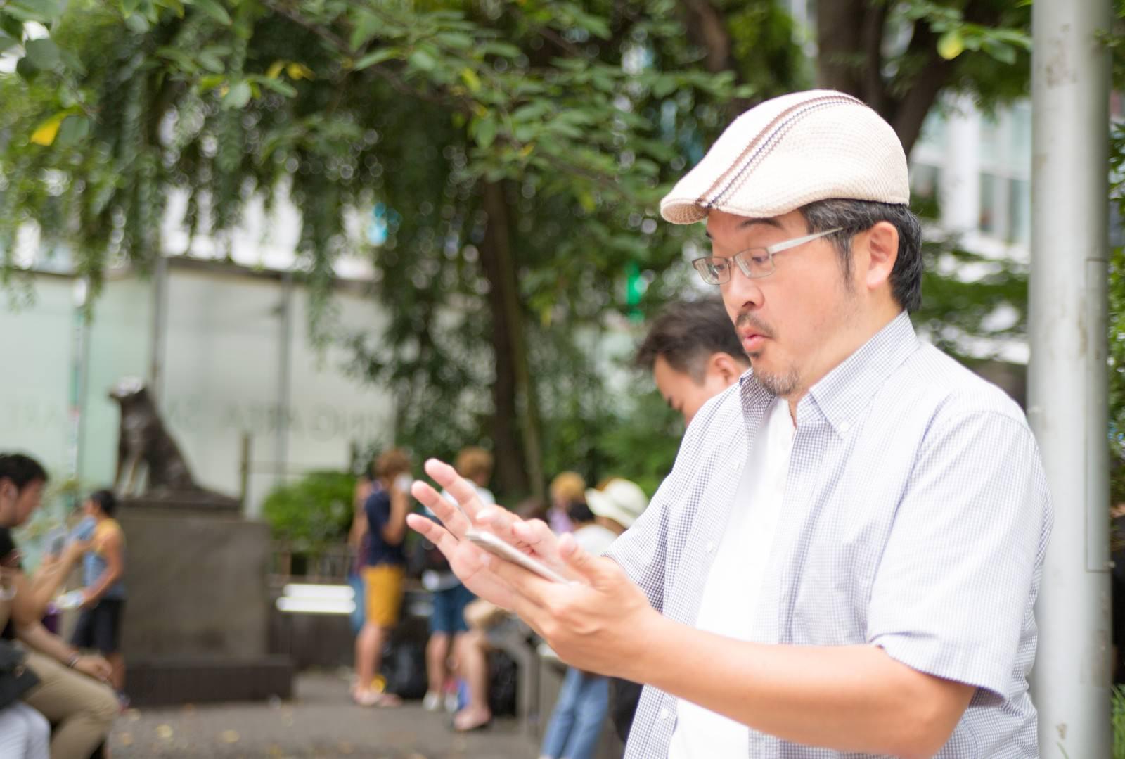 「レアなモンスターをゲットできて興奮するハンチング帽の男性」の写真[モデル:ナリシゲ]