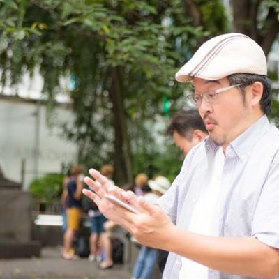 「レアなモンスターをゲットできて興奮するハンチング帽の男性」の写真素材