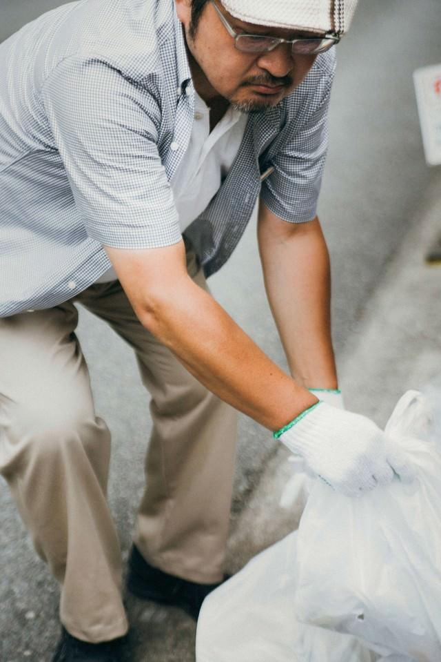 プレイヤーが捨てたゴミを拾うハンチング帽子の男性の写真