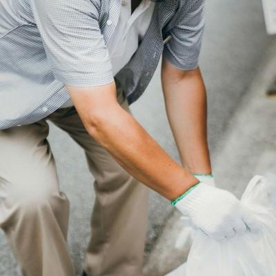 「プレイヤーが捨てたゴミを拾うハンチング帽子の男性」の写真素材