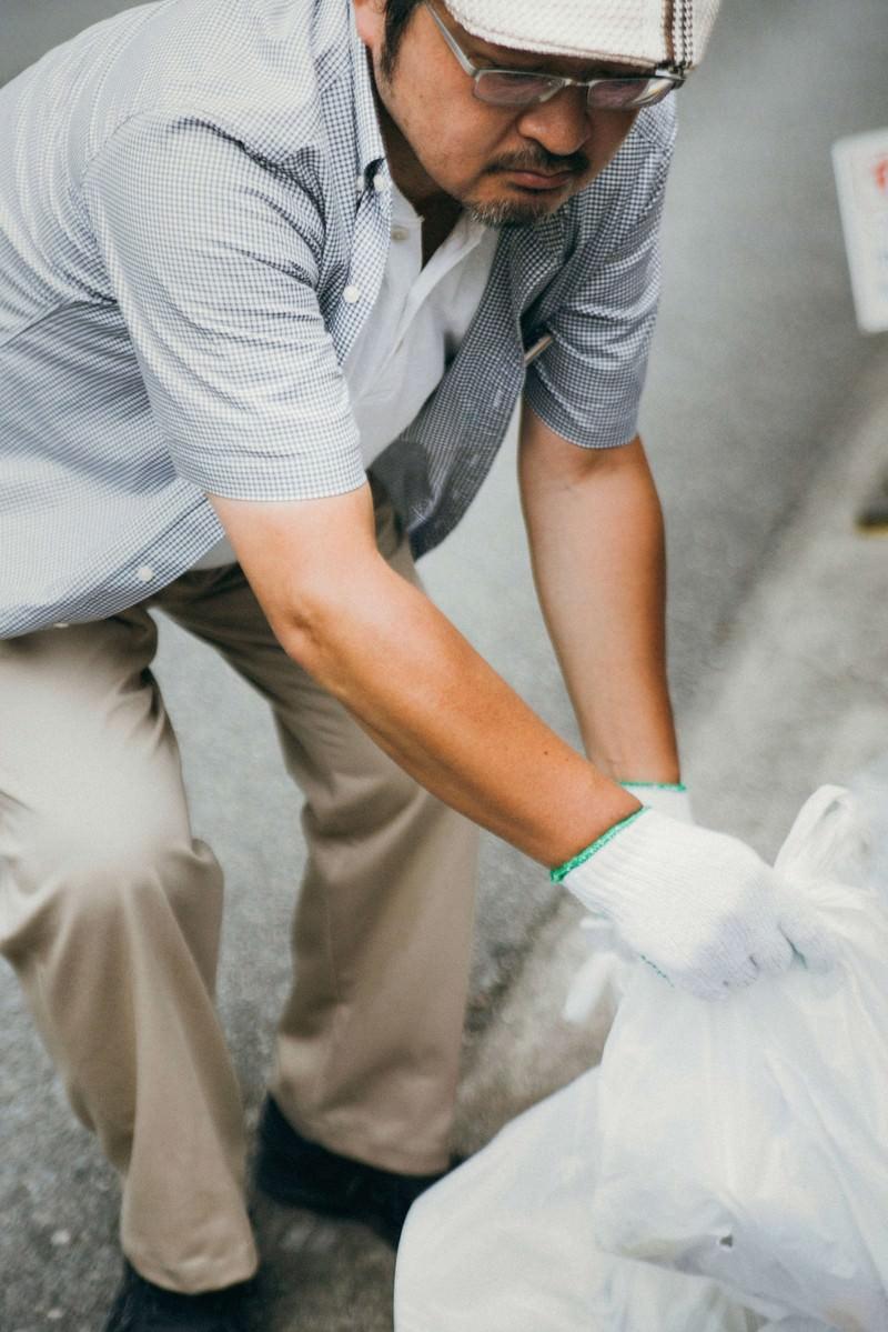 「プレイヤーが捨てたゴミを拾うハンチング帽子の男性」の写真[モデル:ナリシゲ]