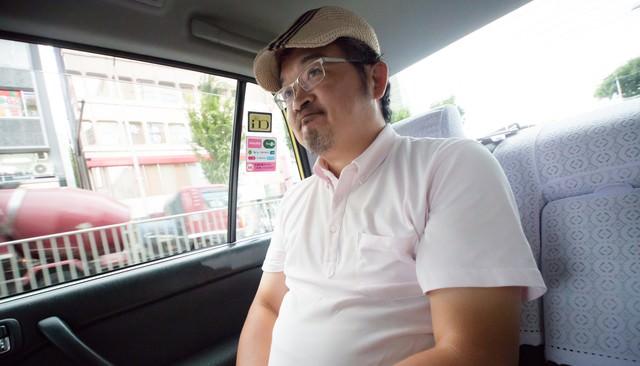 タクシーの運転手に丸くなったと言われて苦笑いをするハンチング帽の男性の写真