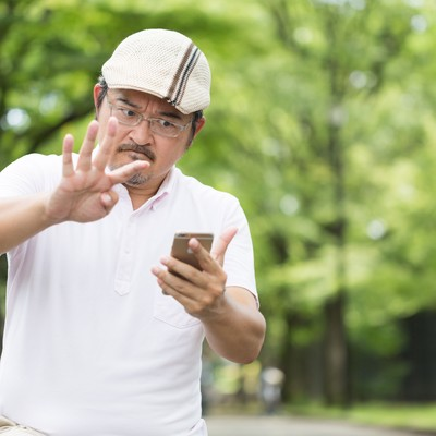 「何度投げても捕まえられない!スマートフォンのゲームに夢中なお父さん」の写真素材