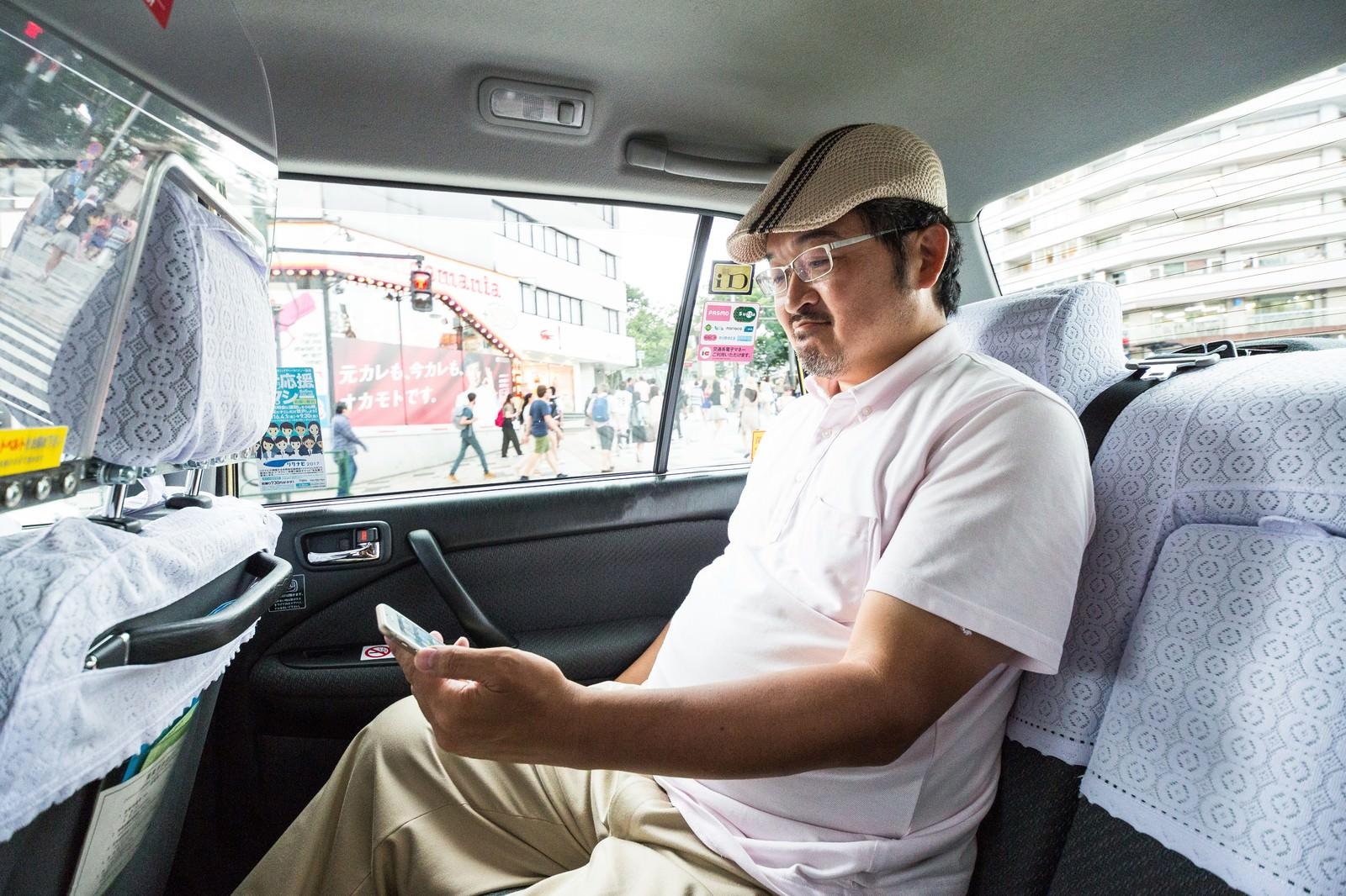 「タクシーに乗車してスマホを操作するハンチング帽のコメンテーター」の写真[モデル:ナリシゲ]