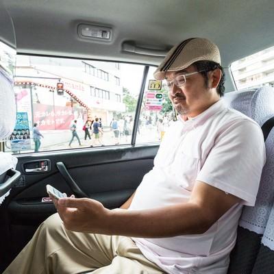 「タクシーに乗車してスマホを操作するハンチング帽のコメンテーター」の写真素材