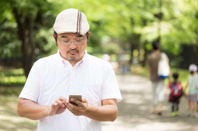 家族が多い公園で、もくもくとモンスター集めをするハンチング帽の男性の写真