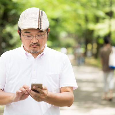 「家族が多い公園で、もくもくとモンスター集めをするハンチング帽の男性」の写真素材