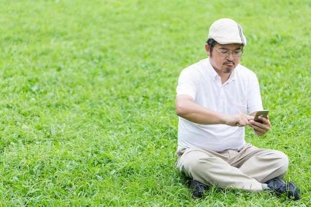 座り込み、ゲームに熱中してしまうハンチング帽の男性の写真