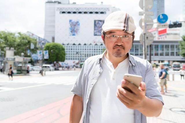 現実は面白いことに満ち溢れていると訴えるハンチング帽の男性の写真
