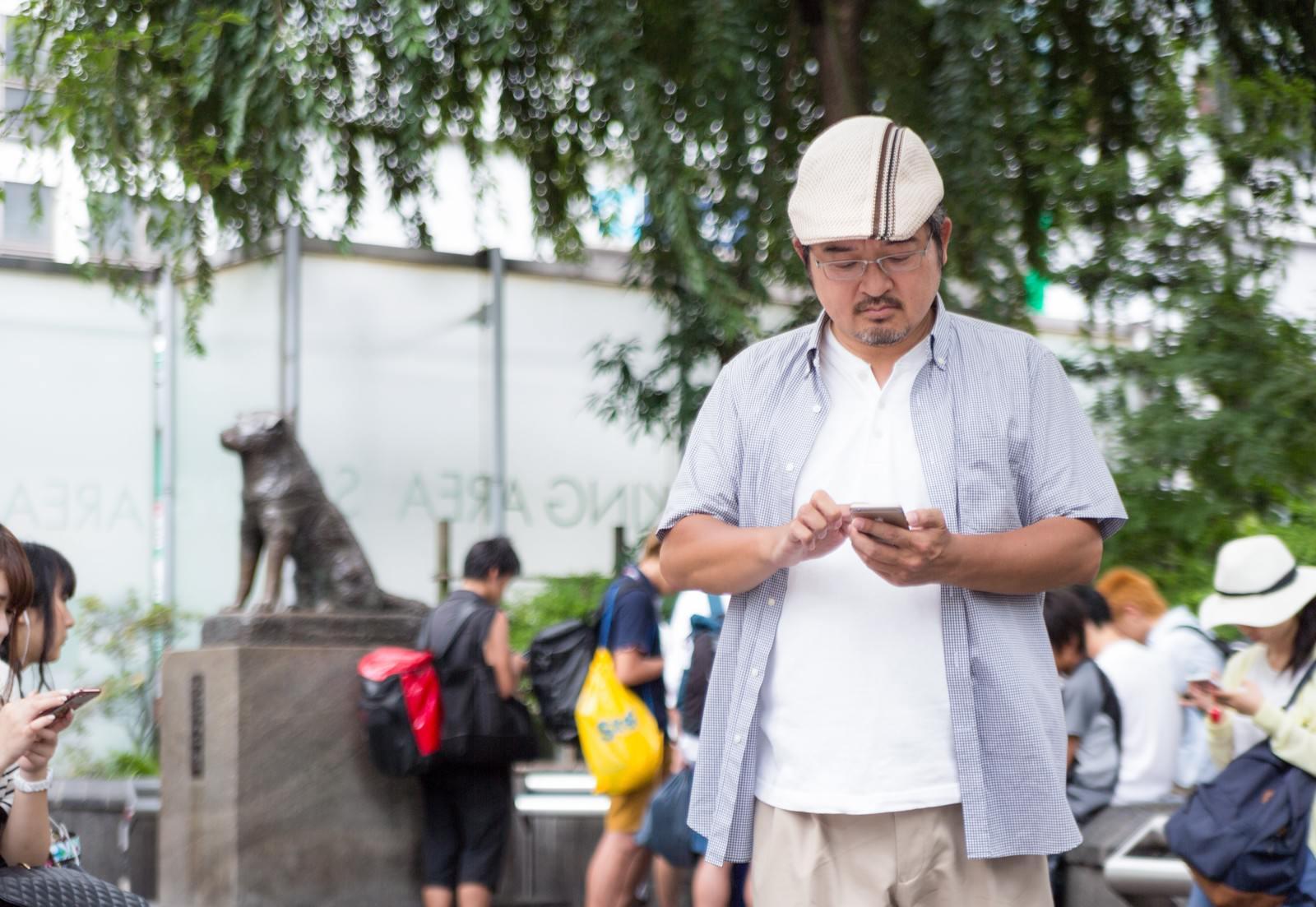 「ポケモノミクスに興じるハンチング帽子の男性」の写真[モデル:ナリシゲ]