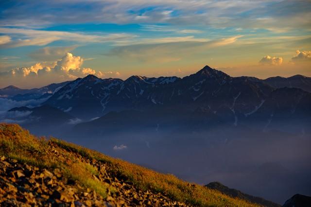 オレンジに染まり始める立山連峰と剱岳の写真