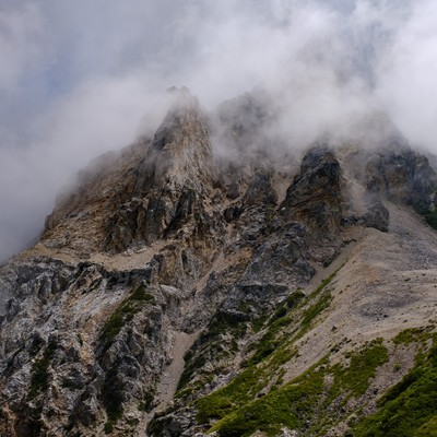 沸き立つガスに包まれた岩山(白馬岳)の写真