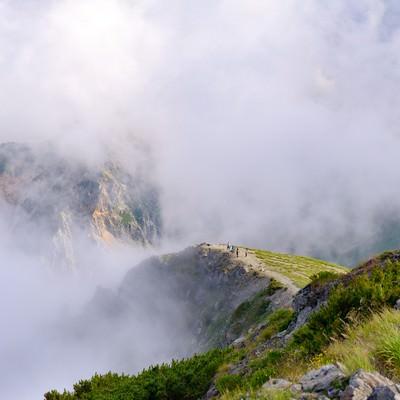 ガスに隠れた杓子岳と切れ間からあられる登山道(杓子岳)の写真