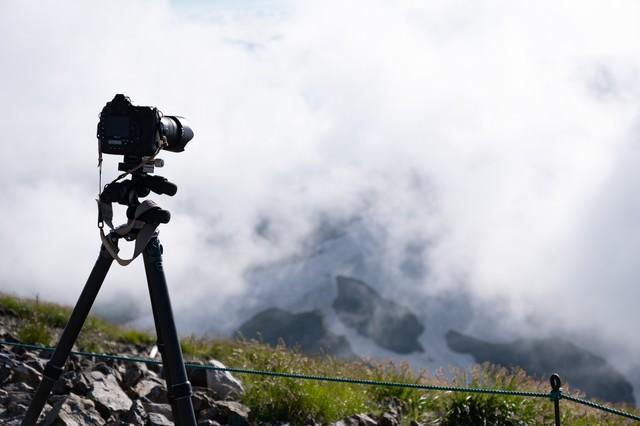 山頂で構える一眼レフカメラと三脚(白馬岳)の写真