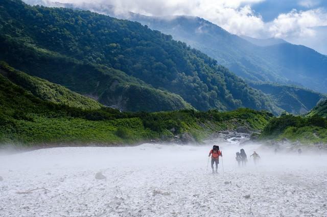 吹き下ろす冷風の白馬大雪渓を登る登山者達(白馬岳)の写真