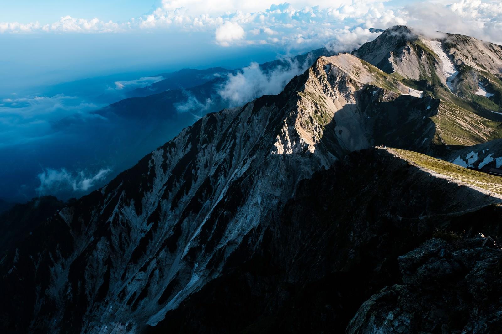 「夕日が当たらない杓子岳の切り立つ山肌」の写真