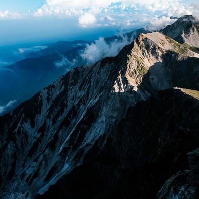 夕日が当たらない杓子岳の切り立つ山肌の写真