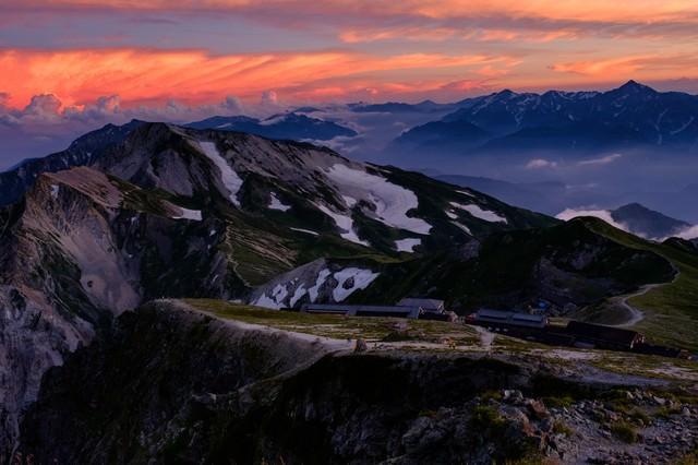 夕日に染まる杓子岳と白馬鑓ヶ岳と立山連峰の写真