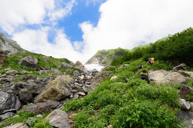 大雪渓を超えて白馬岳山頂を目指す登山者達の写真