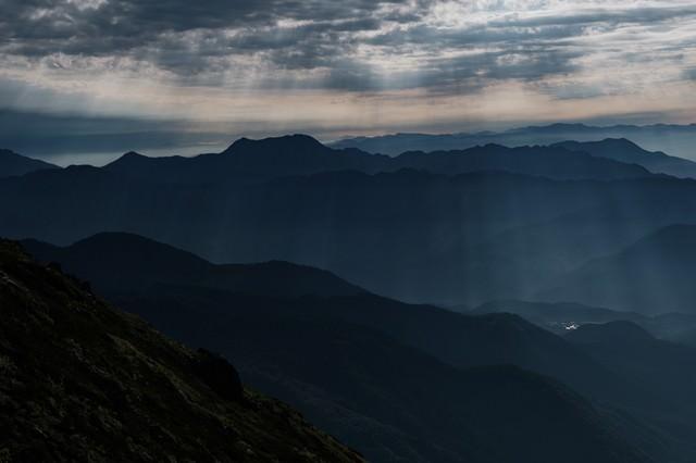 雲間から街へ降り注ぐ光芒の写真