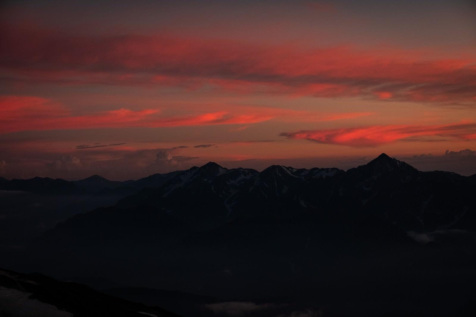 「夕焼けと日没を迎える立山連峰」の写真
