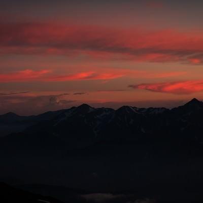夕焼けと日没を迎える立山連峰の写真