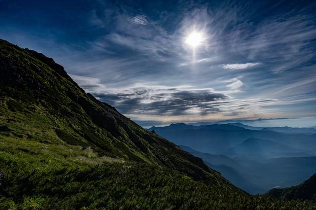 朝の光芒と白馬岳稜線の緑の写真