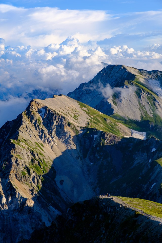 登山道を歩く登山者と杓子岳の写真