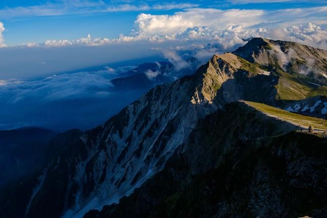 雄大な白馬連峰と切り立つ傾斜面の写真