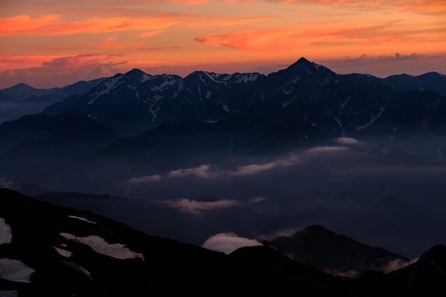 白馬岳から望む夕日に染まる立山連峰の写真
