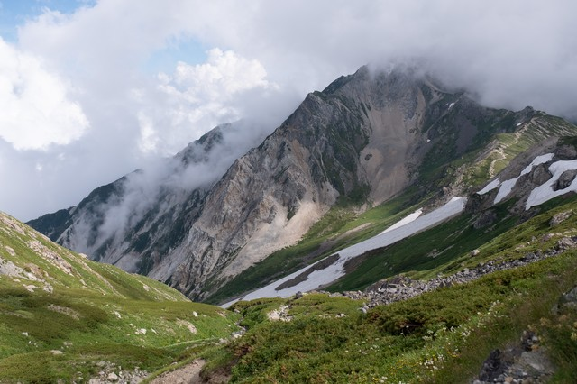 白馬岳(しろうまだけ)の雪渓と沸き立つ雲間に見える山々(白馬岳)の写真