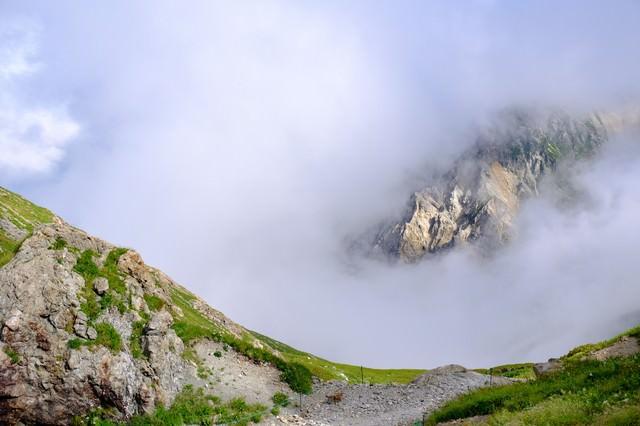 白馬岳山頂からみたガスの合間の岩山の写真