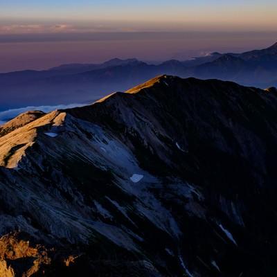 白馬岳山頂から望む夕日に染まる稜線の写真