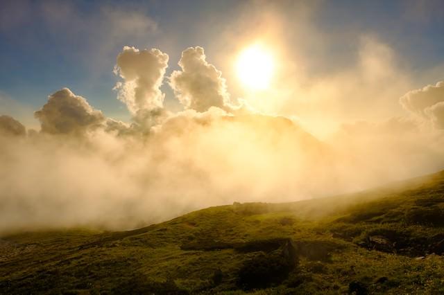 白馬岳稜線の沸き立つ雲の中の夕日の写真