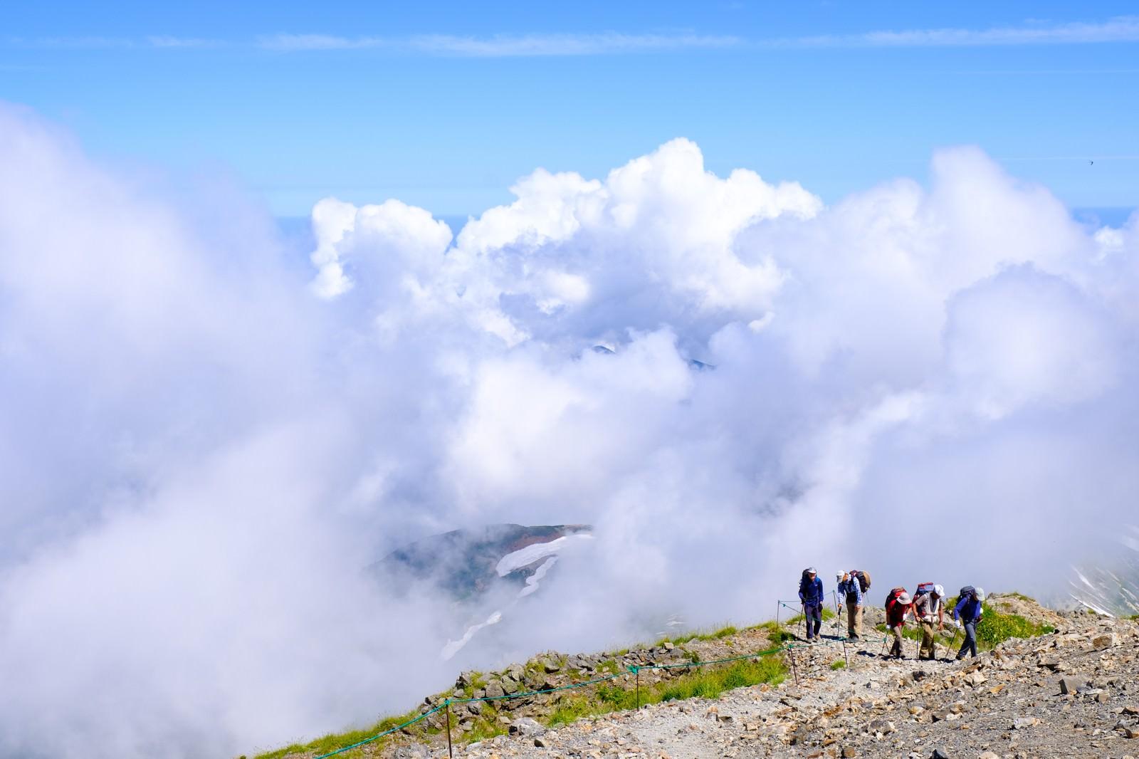 「白馬岳稜線を歩く登山者の後ろに迫る雲」の写真