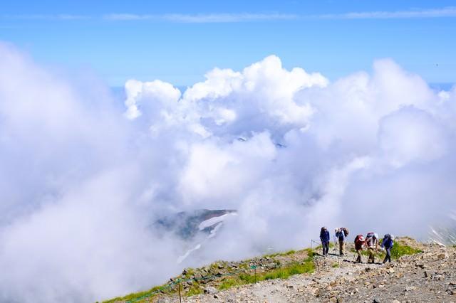 白馬岳稜線を歩く登山者の後ろに迫る雲の写真