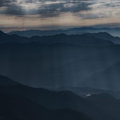 山間部の街へ降り注ぐ光芒の写真