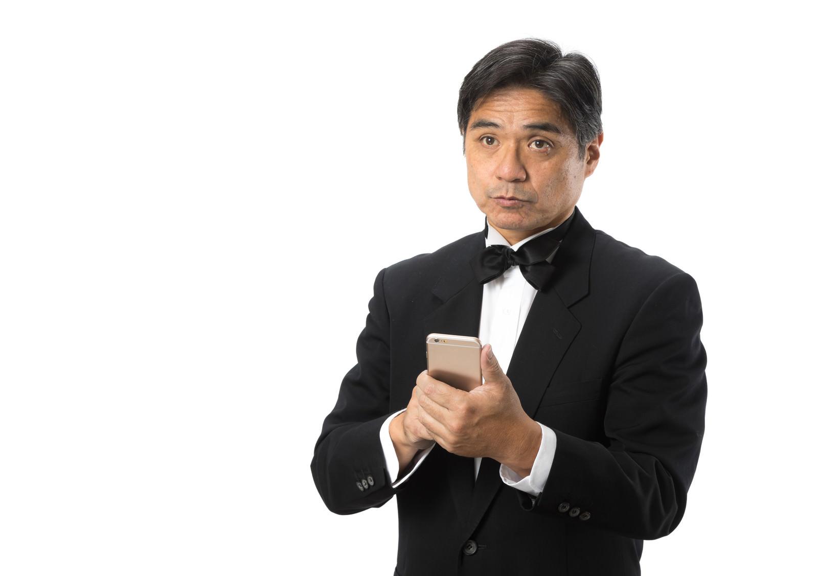 「スマートフォンで翻訳しながら対話する執事」の写真[モデル:よたか]