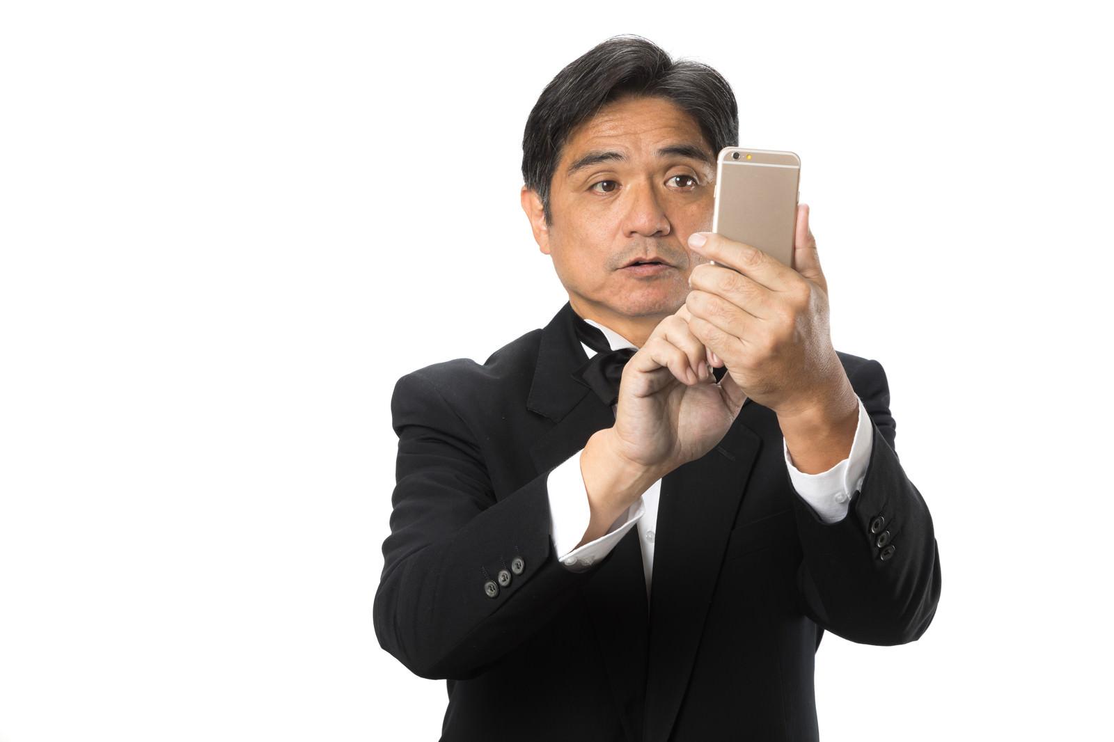 「スマートフォンの操作に慣れない執事」の写真[モデル:よたか]
