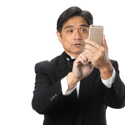 スマートフォンの操作に慣れない執事の写真