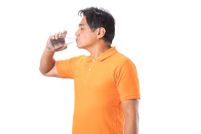 勢いよく水を飲む中年男性の写真