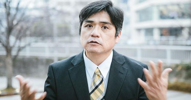 屋外で部下に説明する中年上司の写真