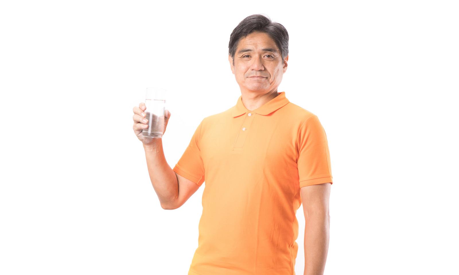 「コップ一杯の水と健康的な中年の男性」の写真[モデル:よたか]
