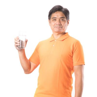 「コップ一杯の水と健康的な中年の男性」の写真素材