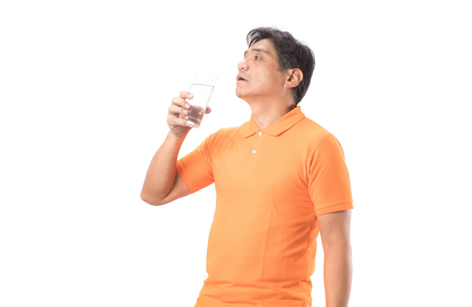 「水を飲んでほっと一息するお父さん」の写真[モデル:よたか]