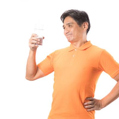 「こまめな水分補給が健康の証!と胸をはる中年男性」の写真素材