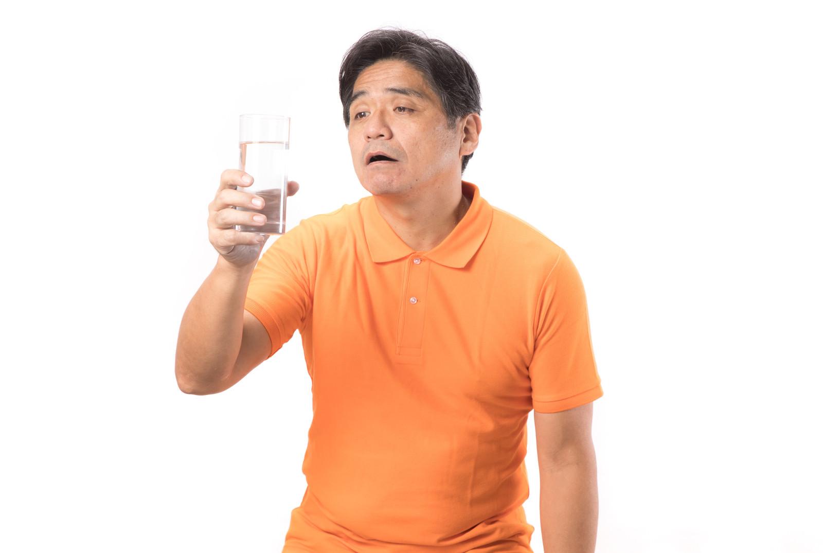 「熱中症気味の男性がコップ一杯の水を飲む」の写真[モデル:よたか]