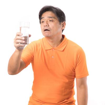 「熱中症気味の男性がコップ一杯の水を飲む」の写真素材